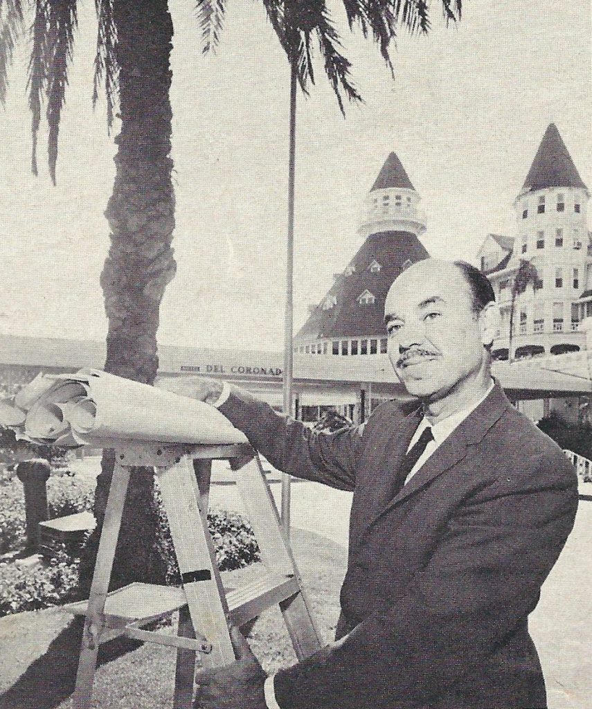 A black and white photo of Al Goodman standing in front of the hotel with his renderings in-hand